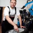 Mechanic fixing tyre in car service — Stock Photo #11986157