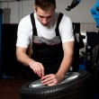 Mechanic fixing tyre in car service — Stock Photo #11986197