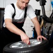 Mechanic fixing tyre in car service - Zdjęcie stockowe