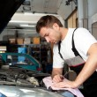 Auto mechanic checking car in service - Stock Photo