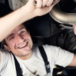Auto mechanic working under the car smiling - Stock Photo