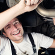Auto mechanic working under the car smiling — Stock Photo