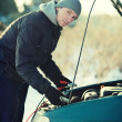 Man fix broken car with accumulator wire in winter - Stock Photo
