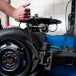 Mechanic changing a car tire closeup - Stock Photo