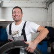 Mechanic smiling at work - Stock Photo