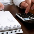 Counting income on calculator — Stock Photo