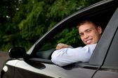 Young man in the car smiling — Stock Photo