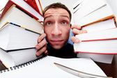 Funny student looking from behind the books — Stock Photo
