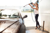 Young woman washing the car — Foto de Stock