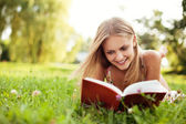 Young woman reading book at park lying down on grass — Stock Photo