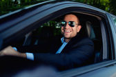 Businessman in car smiling — Stock Photo