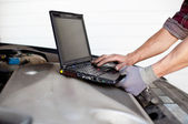 Car mechanic with laptop — Stockfoto