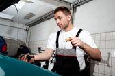 Mechanic checking engine oil — Stock Photo