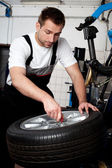 Mechanic fixing tyre in car service — Stock Photo