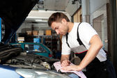 Auto mechanic checking car in service — Stockfoto