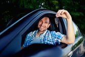 Young man with keys of new car smiling — Stock Photo