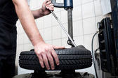Mechanic changing a car tire closeup — Stock Photo