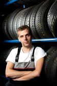 Young mechanic standing next to tire shelves in tire store — Stock Photo