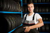 Auto mechanic carrying tire in car service — Stock Photo
