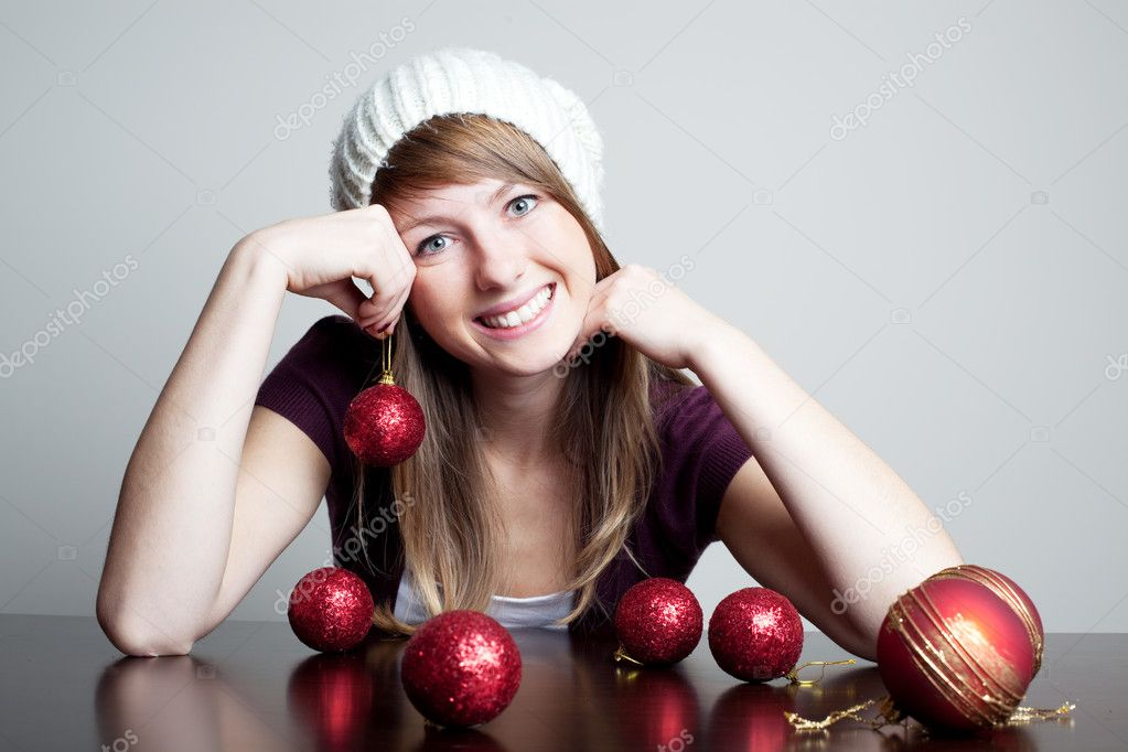 Beautiful woman holding christmas bauble and smiling. Choosing christmas decoration — Lizenzfreies Foto #11988997