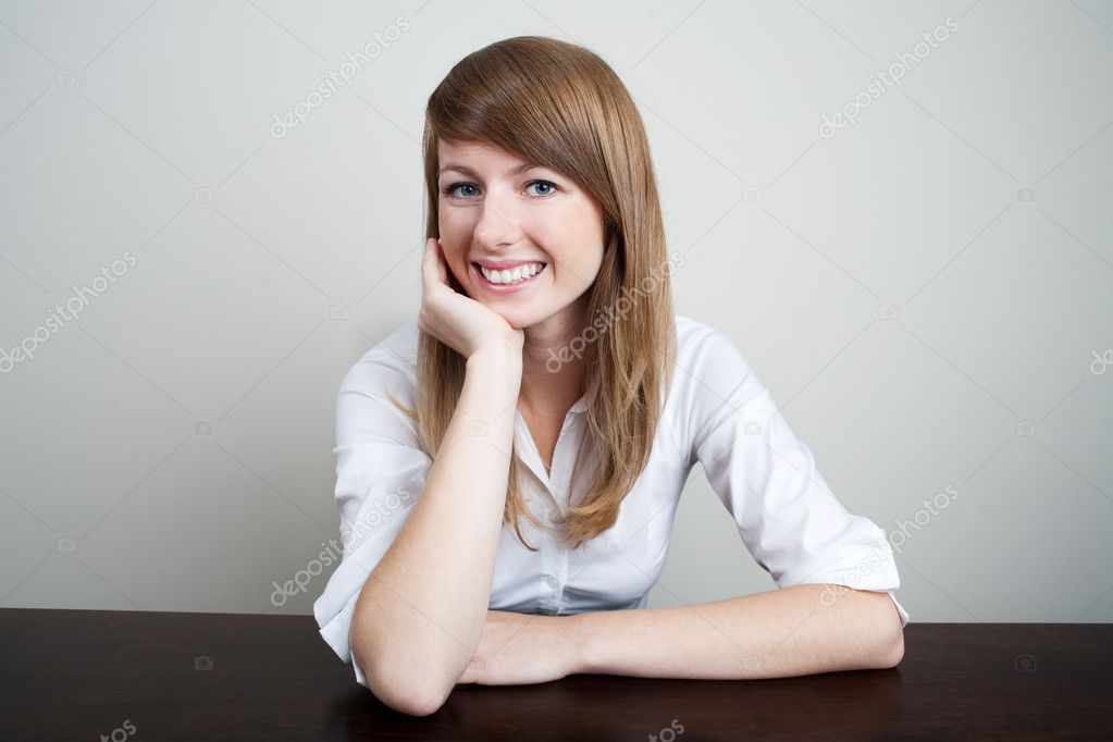 Beautiful bussiness woman siiting at table smiling — Stock Photo #11989331