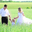 Couple with a baby in a field of wheat - Foto Stock