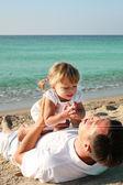 Vater mit Baby am Ufer des Meeres — Stockfoto