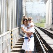 A young mother with her daughter on the railway - Stock Photo