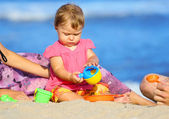 Child playing on the shore of the sea — Stock Photo