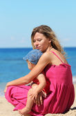 Mother with baby on the shore of the sea — Stock Photo