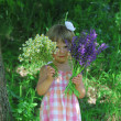 Little girl with flowers outdoors — Stock fotografie