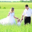 Couple with a baby in a field of wheat — Stock Photo