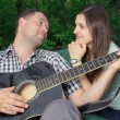 Romantic young couple embracing playing guitar — Stock Photo