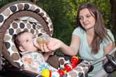 Mother feeding newborn son with feeding bottle — Stock Photo