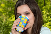 A young woman is drinking from a paper Cup — Stock Photo