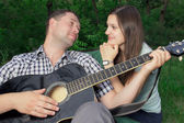 Romantic young couple embracing playing guitar — Foto de Stock