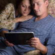 Happy couple sitting together on a sofa , using tablet pc — Stock Photo