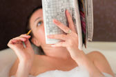 Een vrouw in de badkamer op te lossen een kruiswoordpuzzel — Stockfoto
