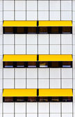 Facade with white tiles and yellow awnings — Stock Photo