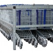 Isolated row of metal shopping carts - Stock Photo