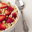 Royalty-Free Stock Photo: Bowl of ring cereals and spoon
