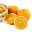 Cropped corn flakes bowl and orange fruit — Stock Photo