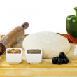 Rolling pin dough and pizza ingredients — Stock Photo