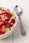 Bowl of ring cereals and spoon — Stock Photo