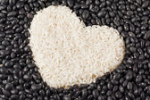 Heart shape rice grains isolated on the dark beans — Stock Photo