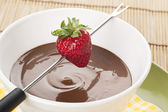 Strawberry on fondue stick and melted chocolate bowl — Стоковое фото