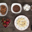 Stock Photo: Chocolates fruits and biscuits on wooden table