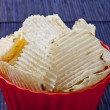 Fried potato chips in red plastic bowl — Stock Photo