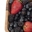 Strawberries blueberries and blackberries in wooden bowl — Stock Photo #12195830