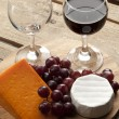 Wooden board with wine glass grapes — Stock Photo